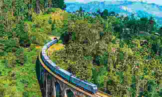 A blue train crosses Nine Arches Bridge (Shutterstock)