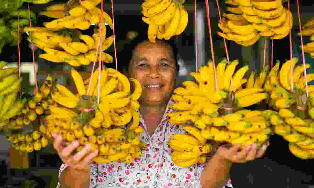 A lady selling bananas in Thailand (Shutterstock)