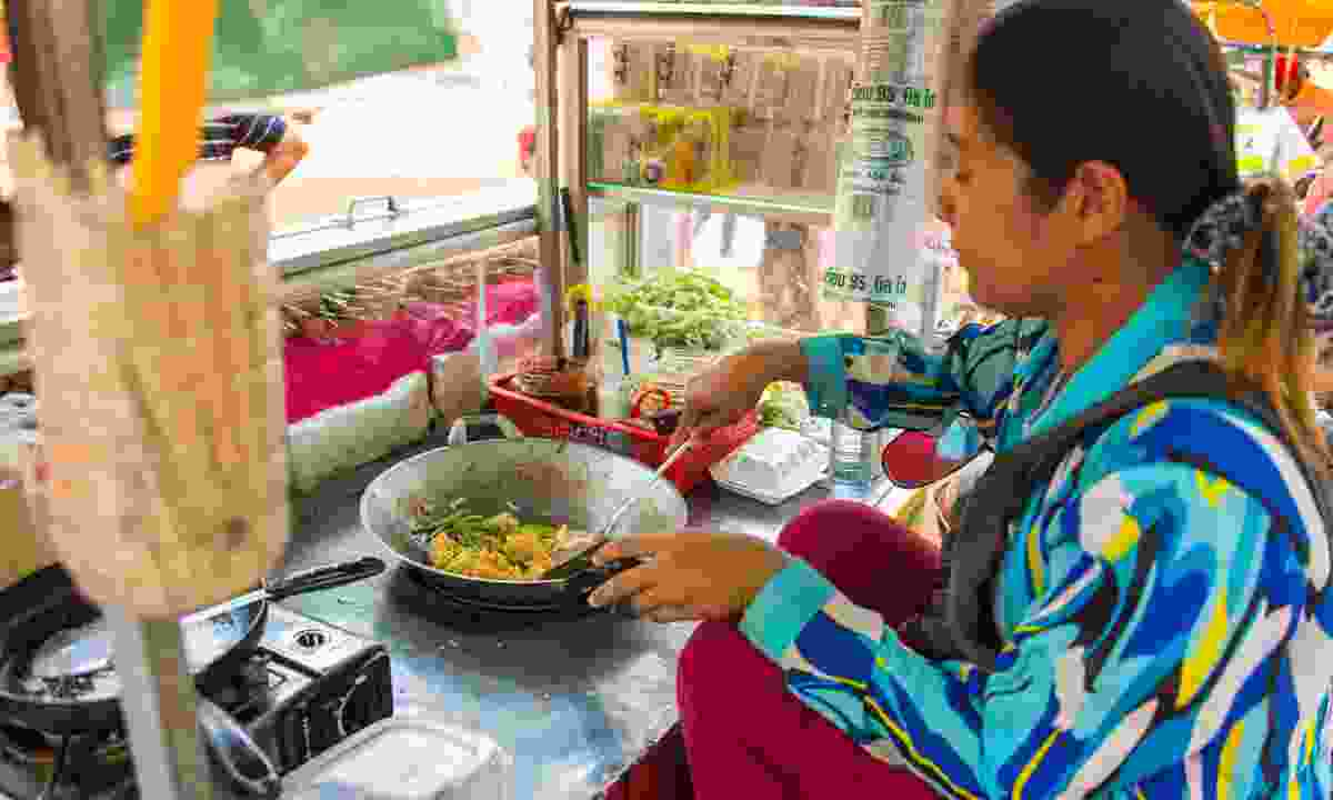 A woman cooking Nom Banh Chok or Khmer noodles (Shutterstock)