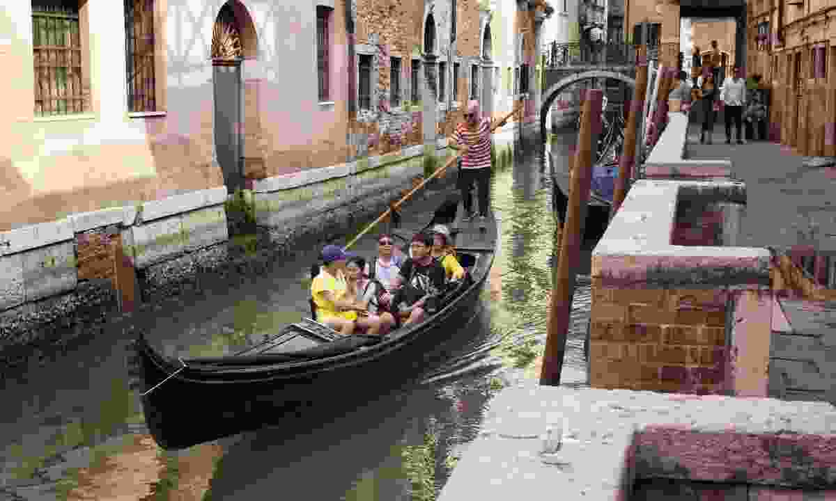 Family riding a gondola in Venice (Dreamstime)