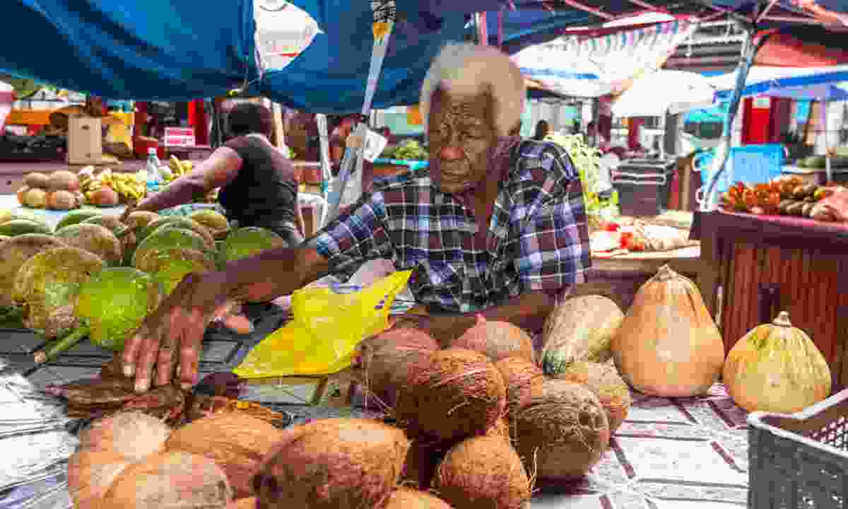 A vendor behind his market stall in the Seychelles (Shutterstock)