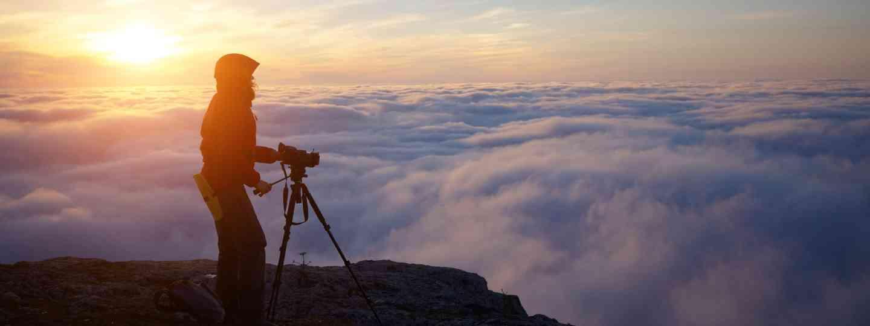 Film maker in mountains at sunrise (Dreamstime)