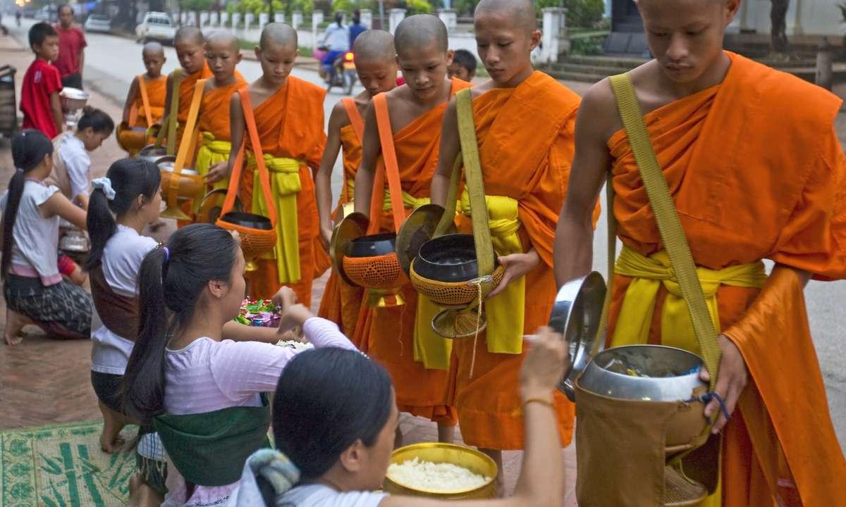 Buddhist monks move through Luang Prabang at dawn (Dreamstime)
