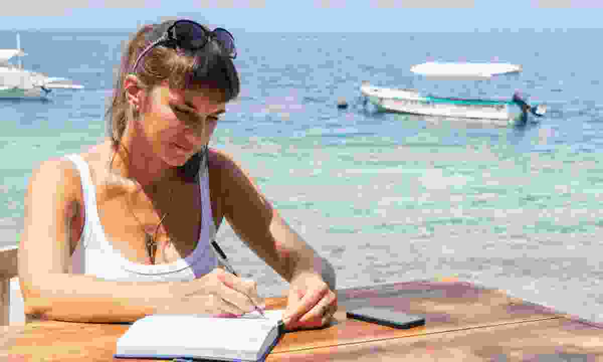 A woman writing in a notepad (Dreamstime)