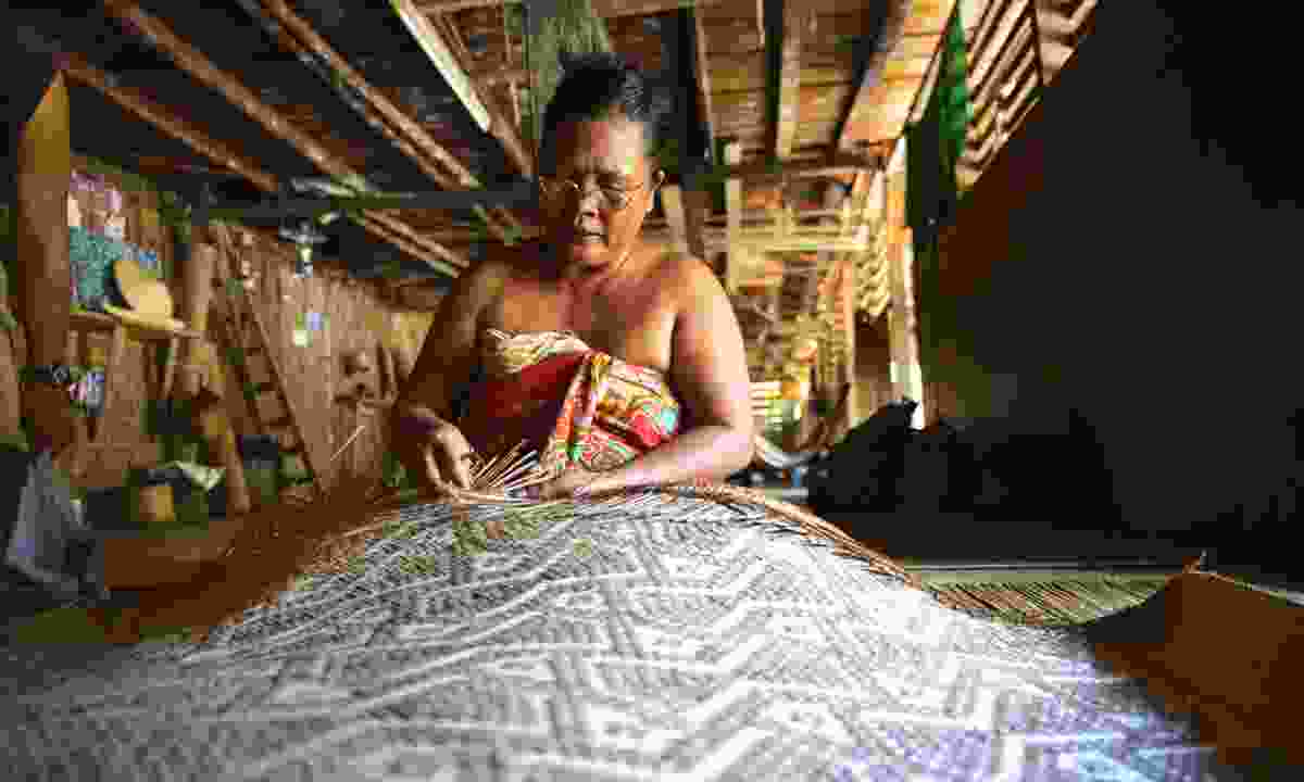 A woman weaves bamboo sleeping mats (Mark Eveleigh)