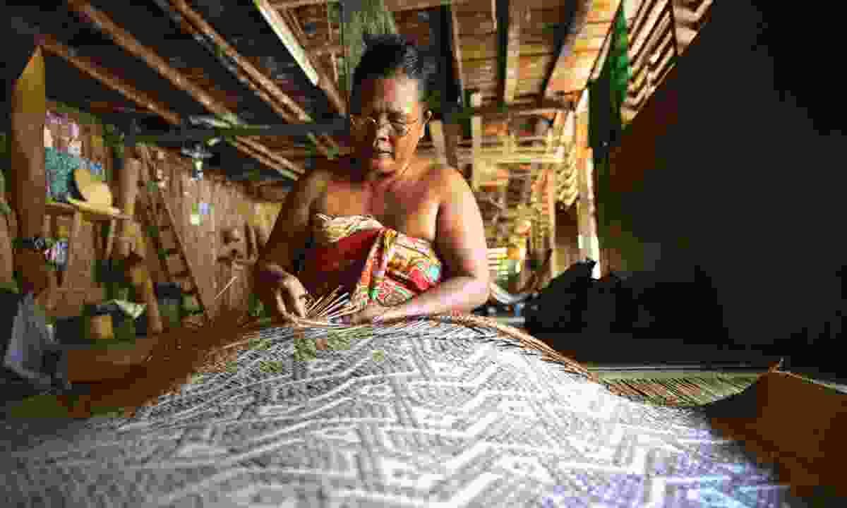 A woman weaves bamboo sleeping mats (Mark Eveleigh)
