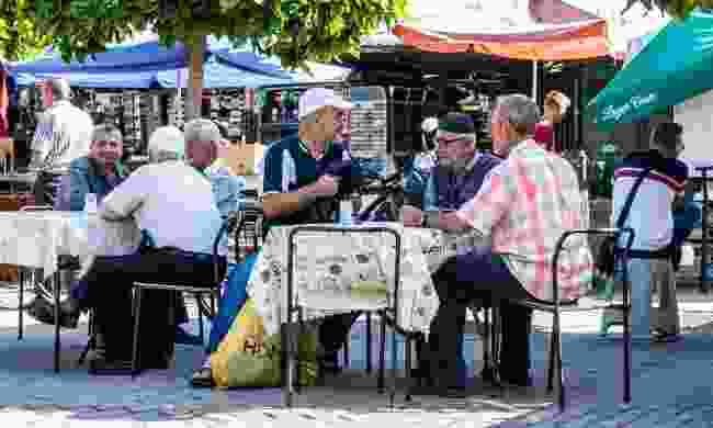 A group of elderly men sit for drinking coffee in Skopje (Shutterstock)