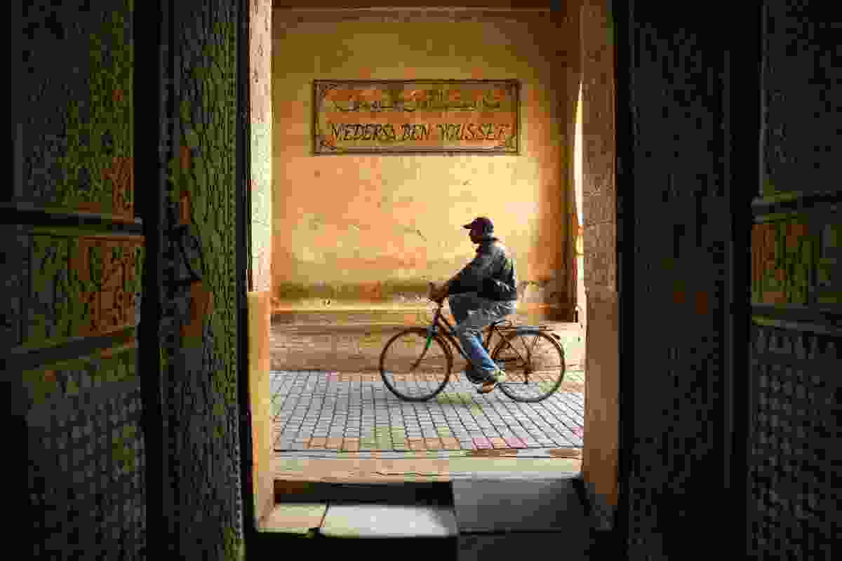 Cyclist passing entrance to Ben Youssef Madrasa in Marrakech, Morocco (Graeme Green)