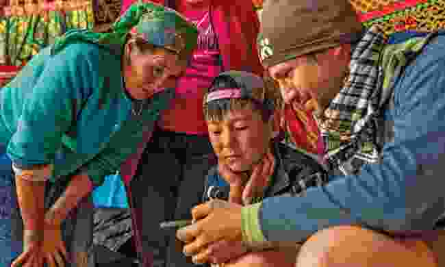Snapper Marcus shows travel images to a family (Henry Wismayer)