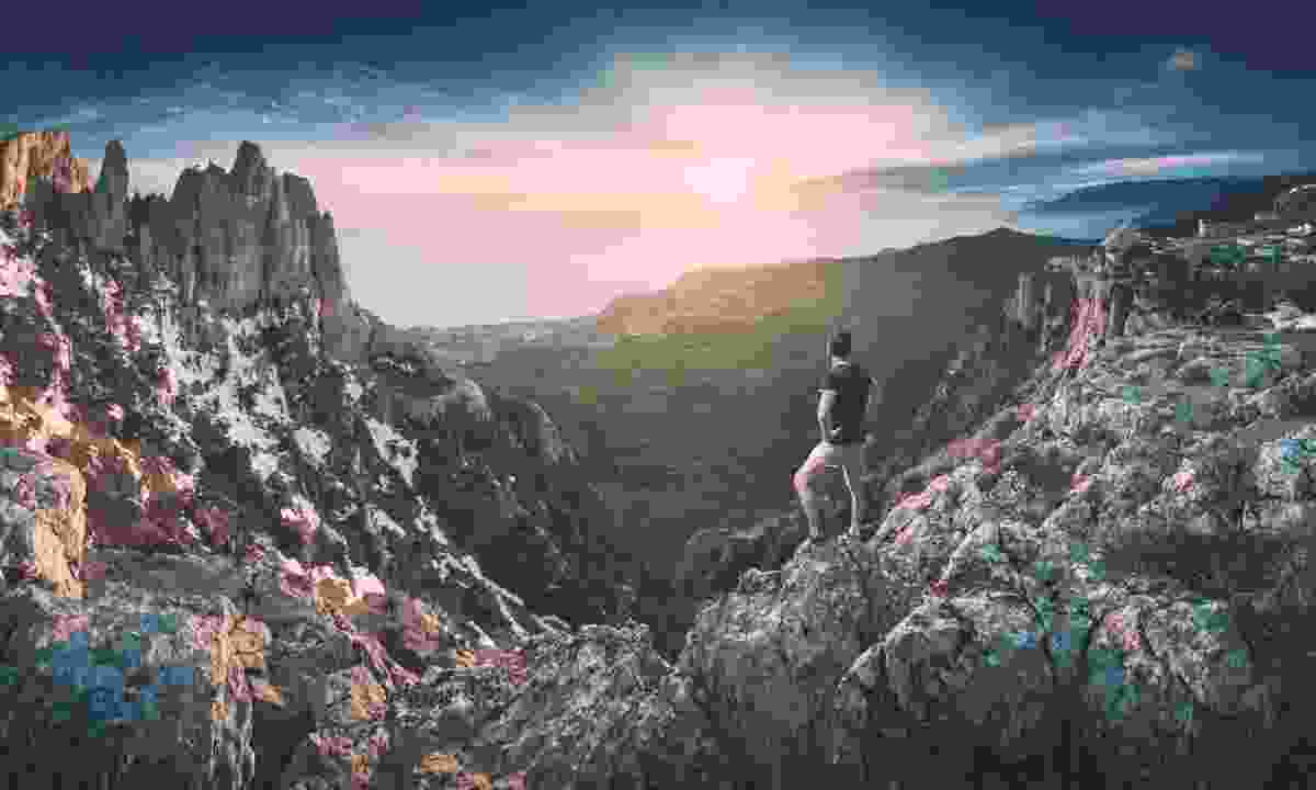 Man standing on a cliff edge in the Crimean mountains (Dreamstime)