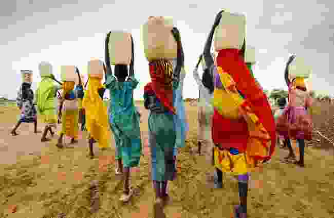 Women walking with water containers on their heads in Tanzania (Shutterstock)
