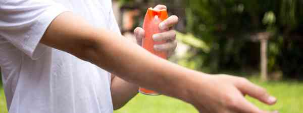 A boy sprays insect repellent on his arm (Dreamstime)