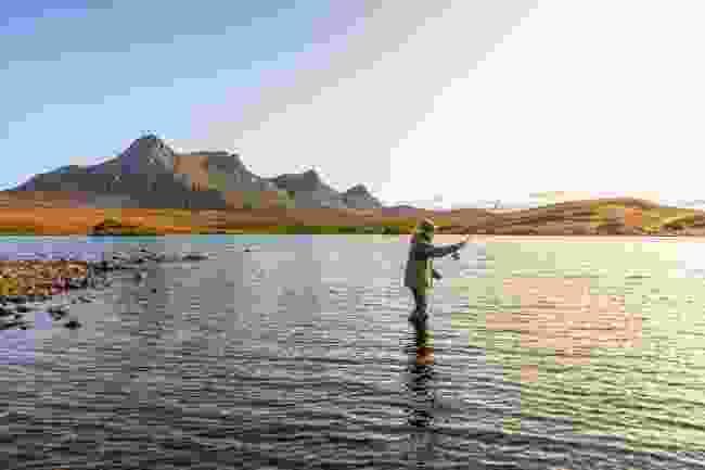 A man fishing on Lochan Hakel with Ben Loyal in the background (Kav Dadfar)