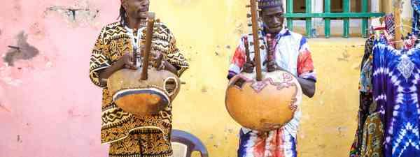 treet musicians playing the kora string instrument (Shutterstock)