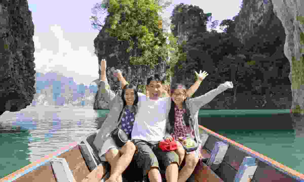 Family enjoying a boat trip in Thailand (Dreamstime)