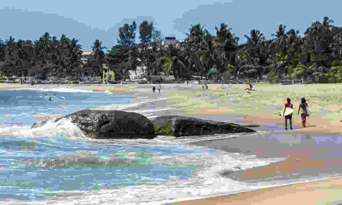Surfers walking along Arugam Bay