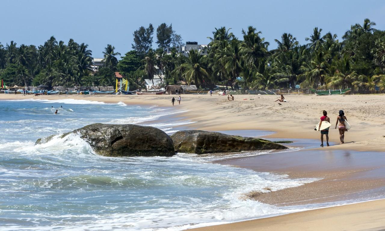 Surferswalking along Arugam Bay