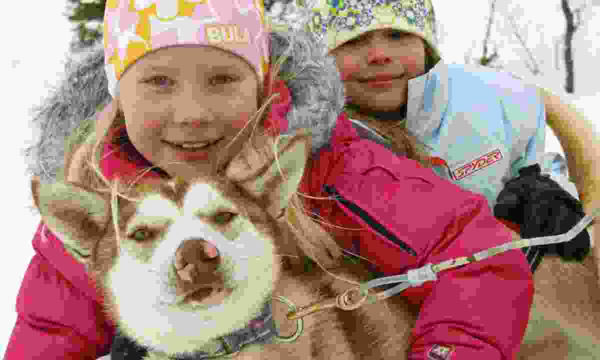 Kids cuddling a husky (KE Adventure Travel)