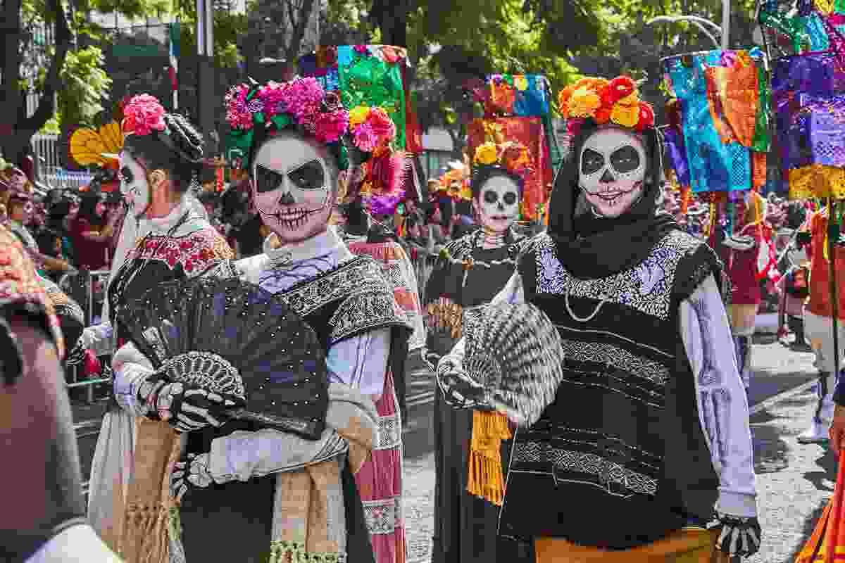 Women painted with sugar skulls on their faces for Día de los Muertos, Mexico (Shutterstock)