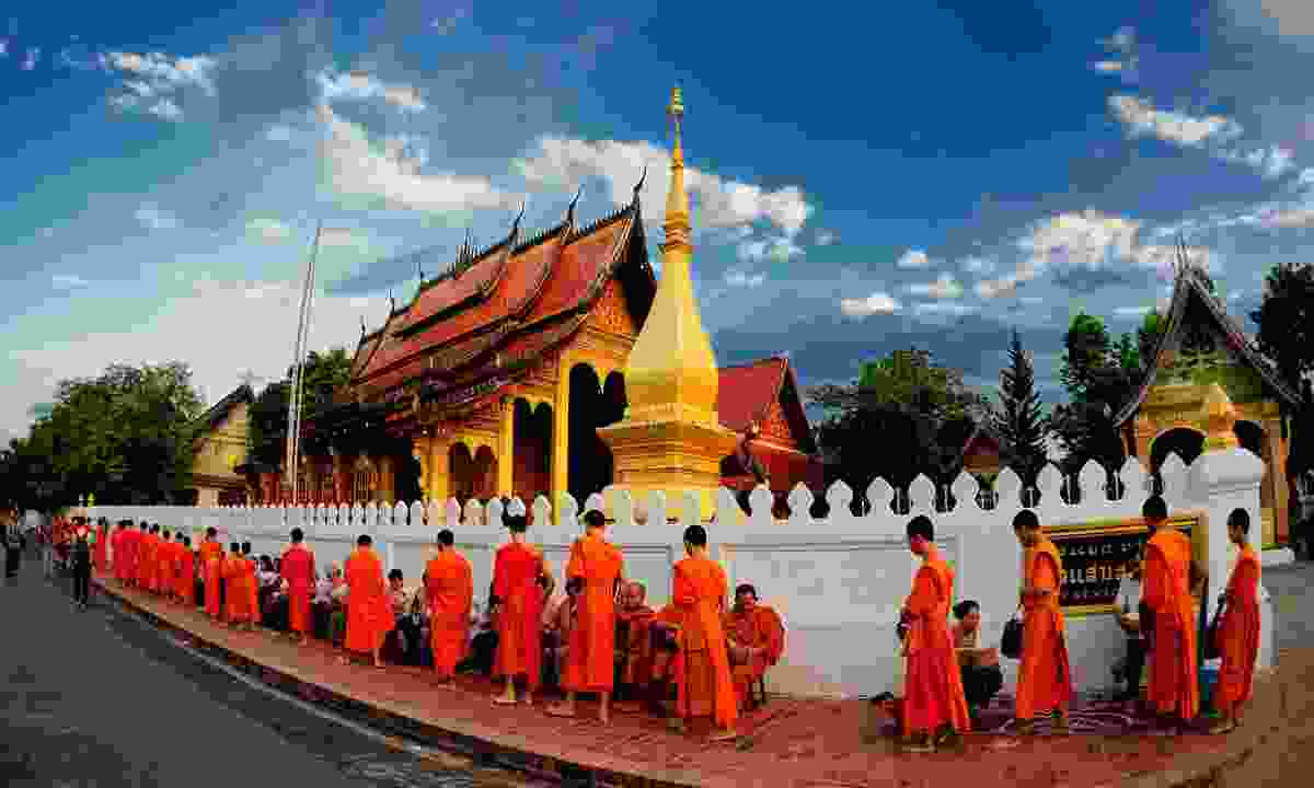 Monks accepting the morning alms (Shutterstock)