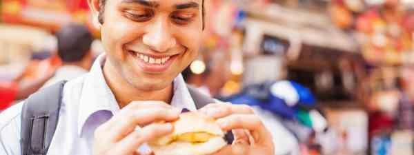 Guy eating street food (Shutterstock)