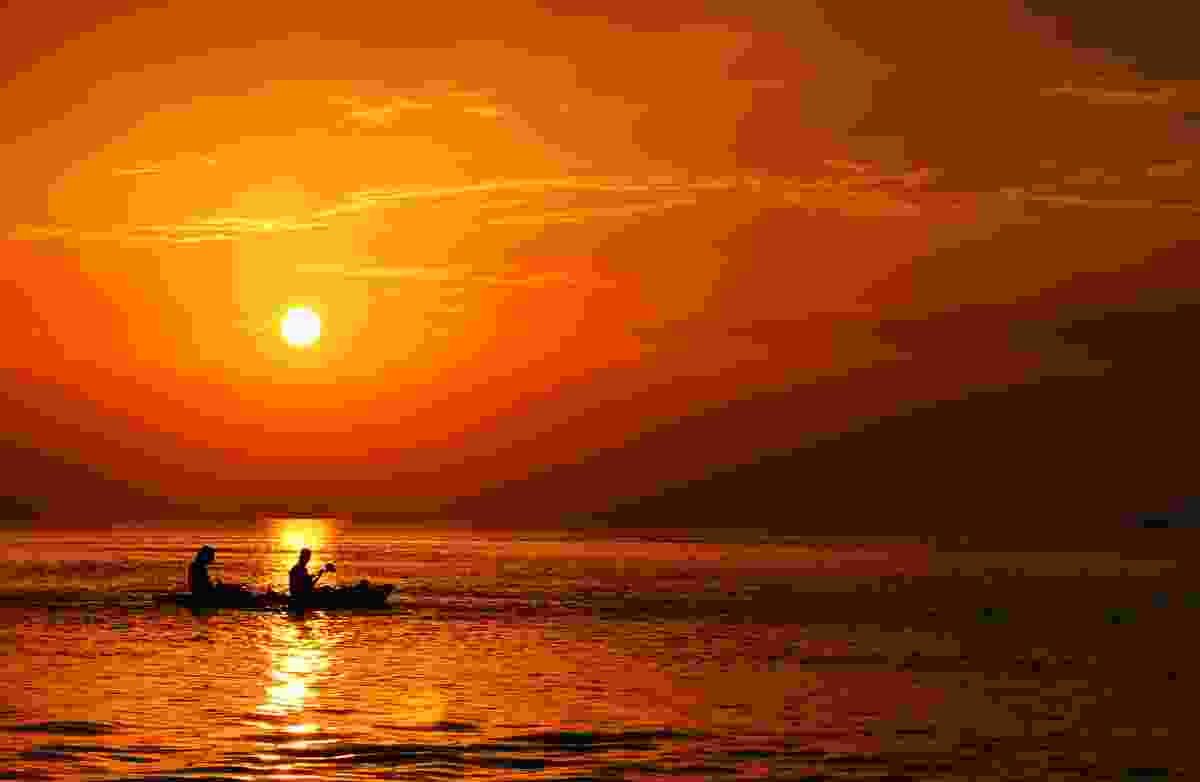 Couple in canoe off the coast of Belize. (Dreamstime)