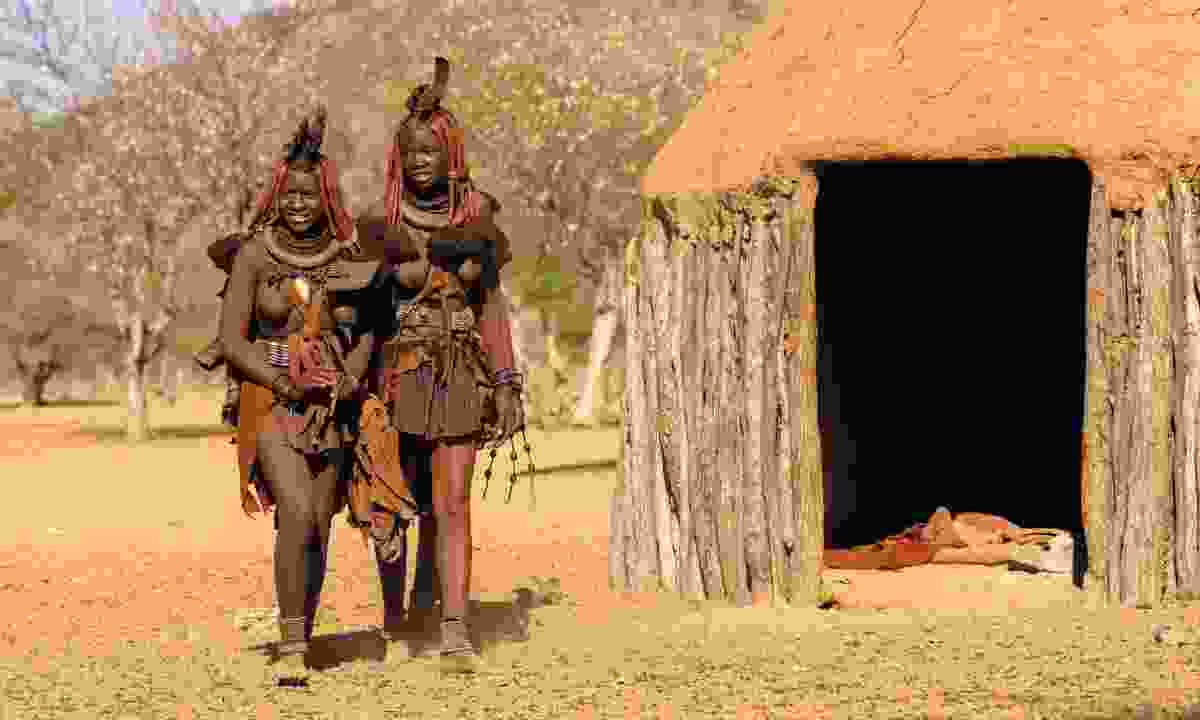 A pair of Himba women wander past the mud-packed huts of a village (Sarah Gilbert)