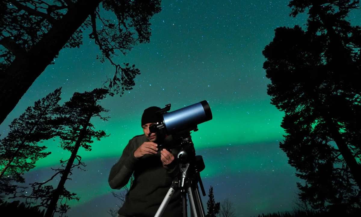 Watching the Northern Lights through a telescope (Dreamstime)