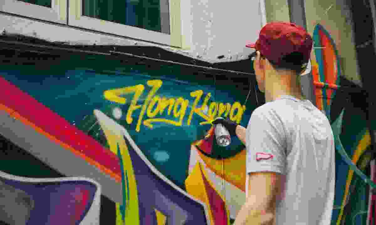 an artisits painiting a wall during Hong Kong's art month in 2018 (Ren Wei)