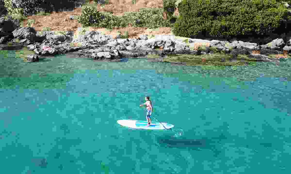 Invigorate your travels by doing something for the first new, such as stand-up paddleboarding in Greece (Shutterstock)