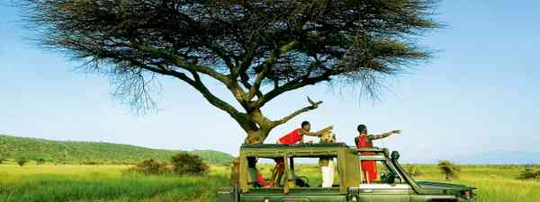A solo traveller looking for animals with Masai scouts in Kenya (Dreamstime)