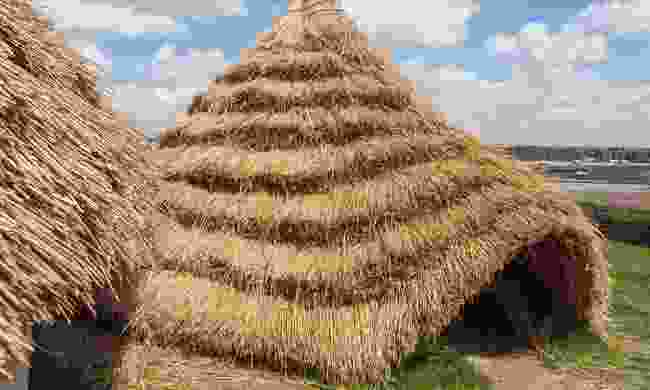 Straw thatched Neolithic-style houses near Stonehenge (Dreamstime)