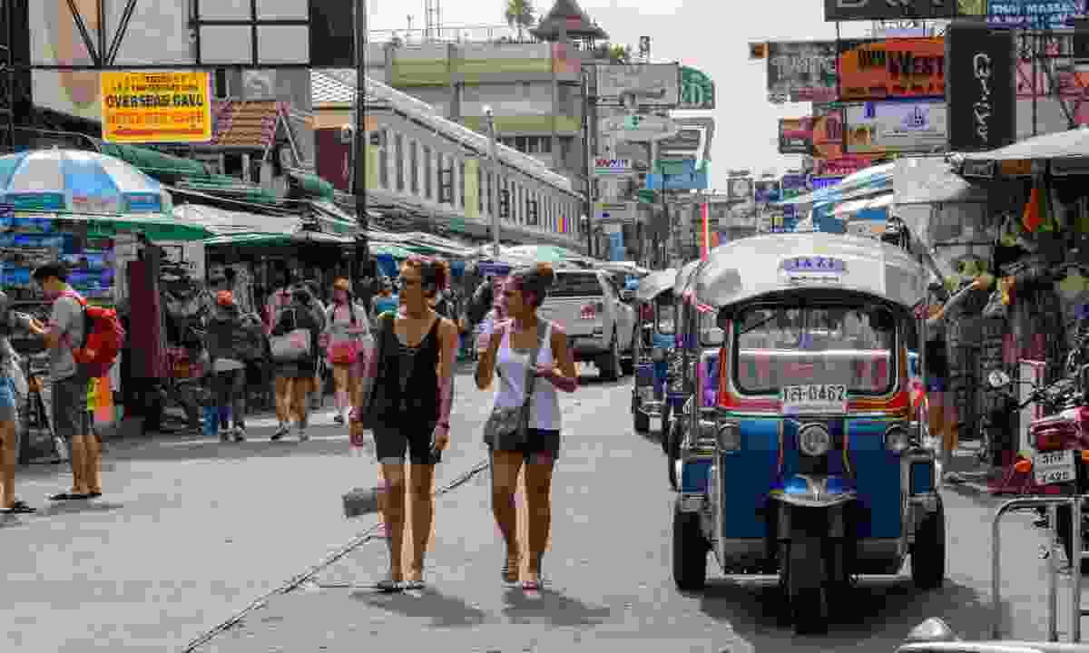 Tourists walk along Khao San Road (Dreamstime)