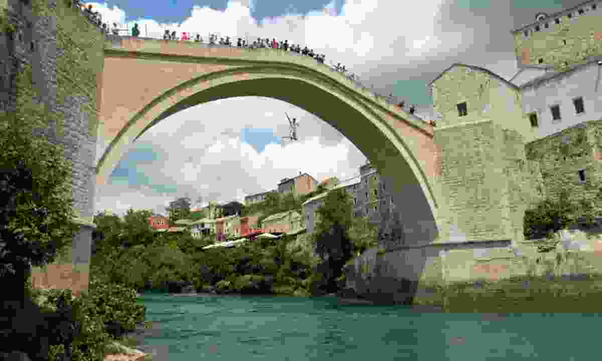 Young tourist jumping off Stari Most (Creative Commons: Sven Wolter)