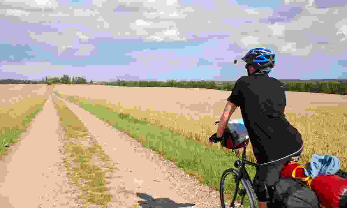 A man on a touring bike loaded up with panniers and gear on a dirt track in Denmark (Dreamstime)