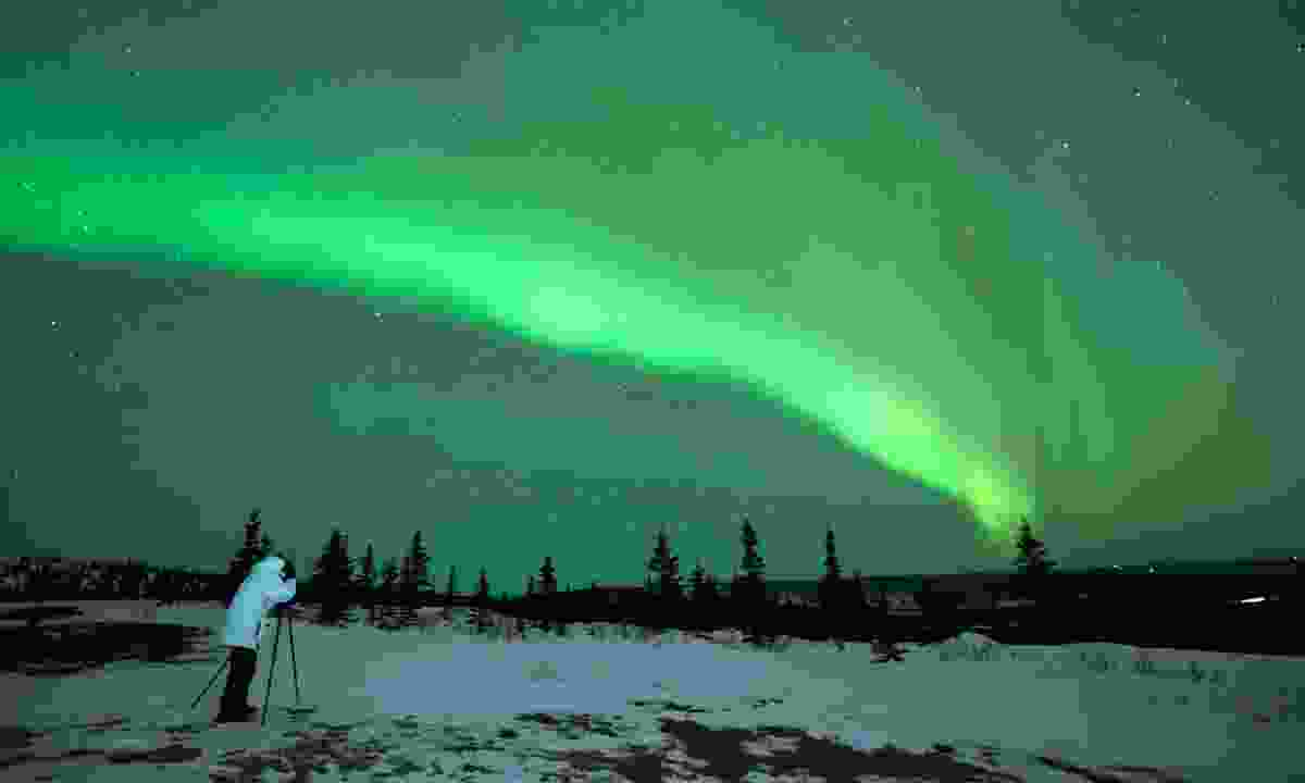 Man photographing the northern lights (Dreamstime)