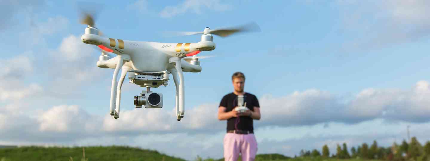 Man in field flying a drone (Dreamstime)
