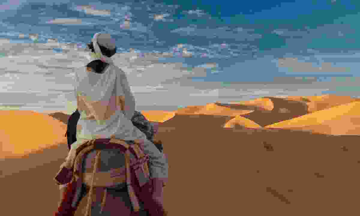 Riding a camel in the Sahara desert (Dreamstime)