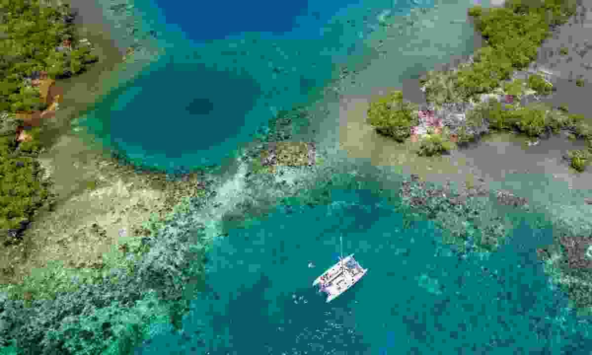 A catamaran floats near a coral reef reserve in Belize (Dreamstime)