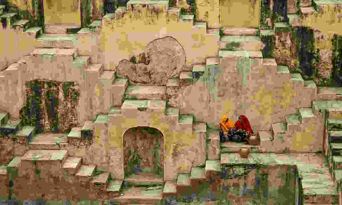 Local standing in the stepwells of Chand Baor (Dreamstime)