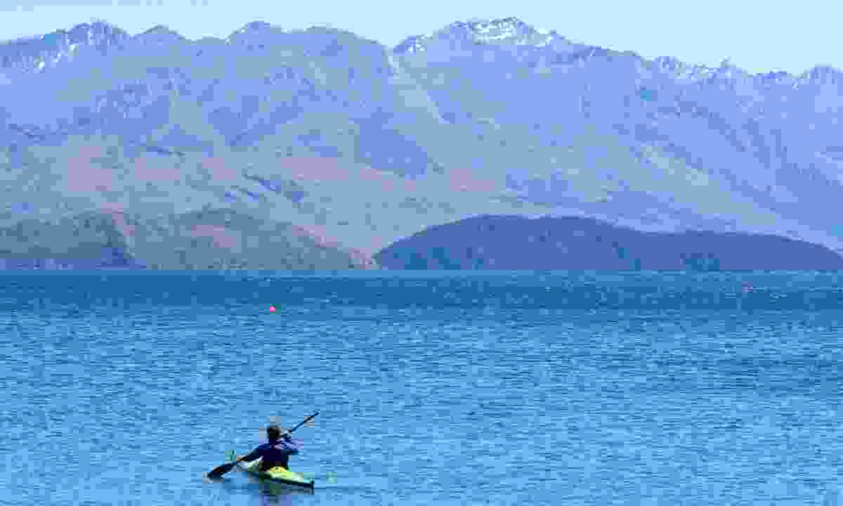 A man paddles a canoes in Wanaha lake, New Zealand (Dreamstime)