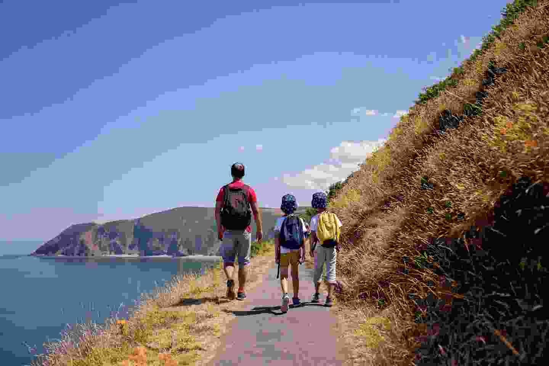 A family walking along the Devonshire coastline (Shutterstock)