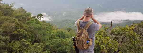 A solo traveller taking pictures on the edge of a cliff (Dreamstime)