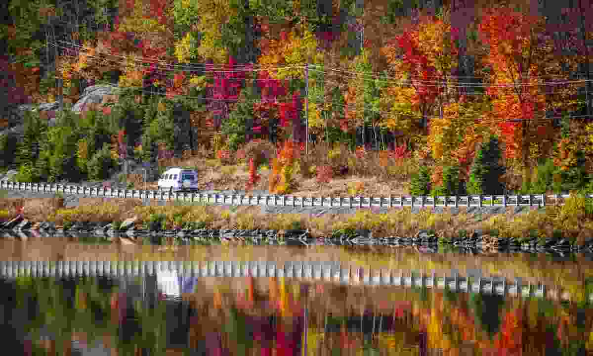 Autumn trees reflected in water in Ontario (Dreamstime)
