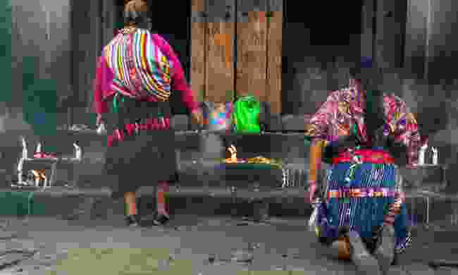 Two women are praying in front of Santo Tomás Chichicastenango (Shutterstock)