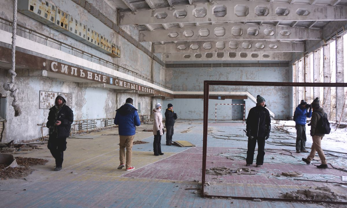 Tourists visit an abandoned gymnasium in Pripyat (Dreamstime)