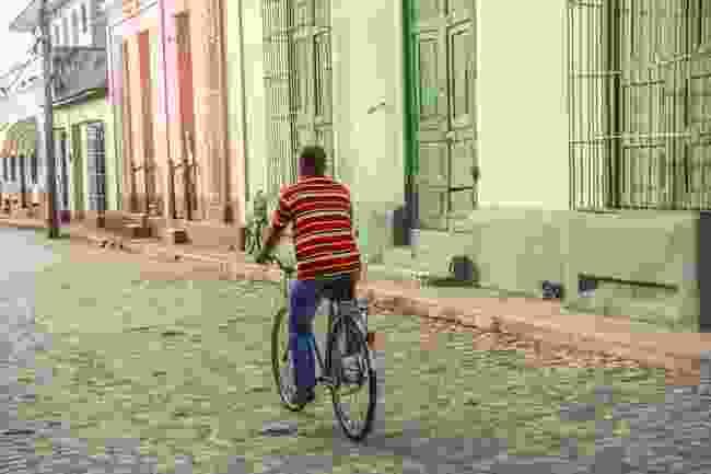 A local cycling through Trinidad in Cuba (Shutterstock)