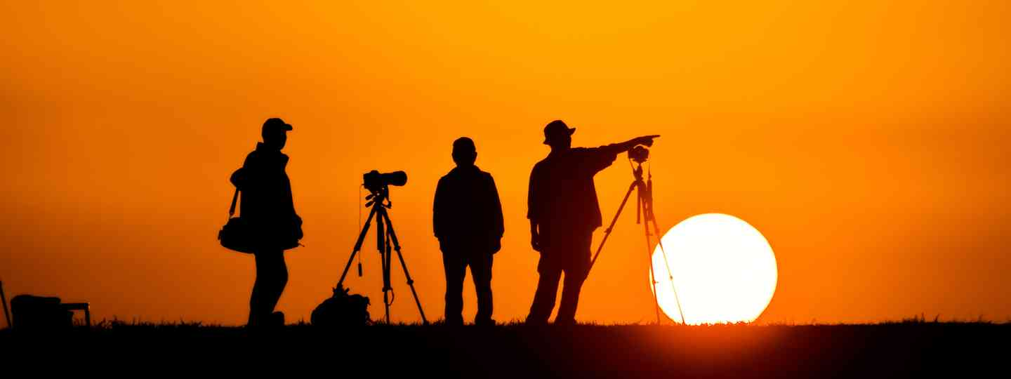 Photographers silhouetted against the setting sun (Dreamstime)