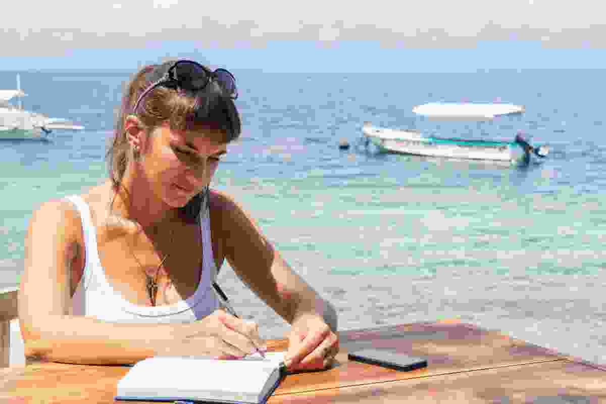 A woman writing at a table in front of a tropical sea (Dreamstime)