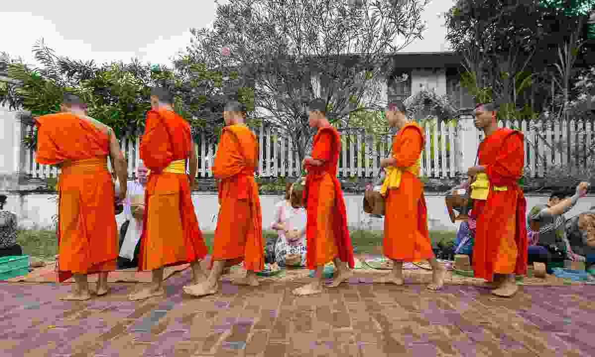 Monks accepting the morning alms (Dreamstime)